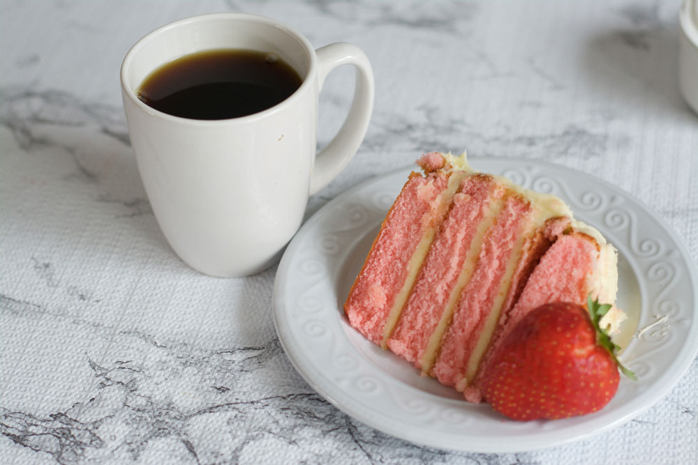 A coffee mug and a plate of strawberry cake